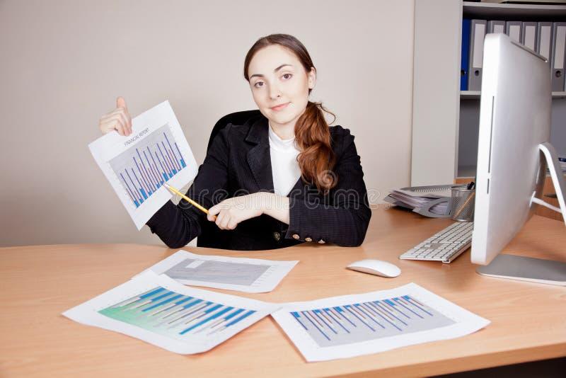 Belle femme d'affaires avec le rapport financier au bureau photo stock
