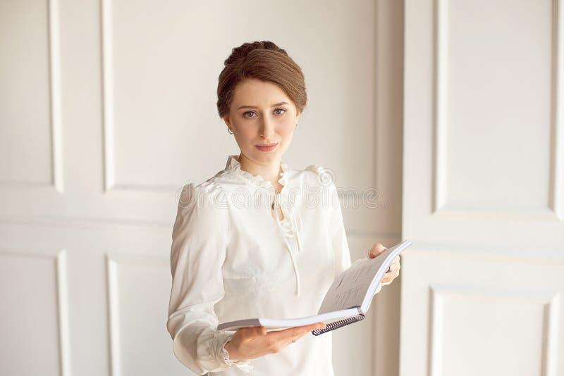 Belle femme d'affaires dans une chemise blanche et un pantalon foncé tenant un dossier avec des documents photo libre de droits