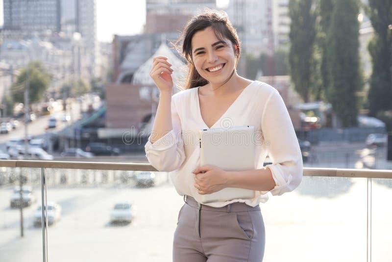Belle femme d'affaires de brune dans la jupe blanche et des pantalons gris de costume travaillant à un comprimé dans des ses main photographie stock