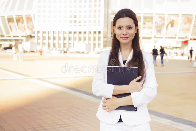 Belle femme d'affaires de brune dans le costume blanc avec le dossier de d photos libres de droits