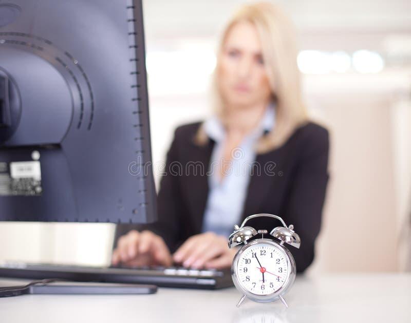 Belle femme d'affaires essayant de respecter une date-limite photographie stock