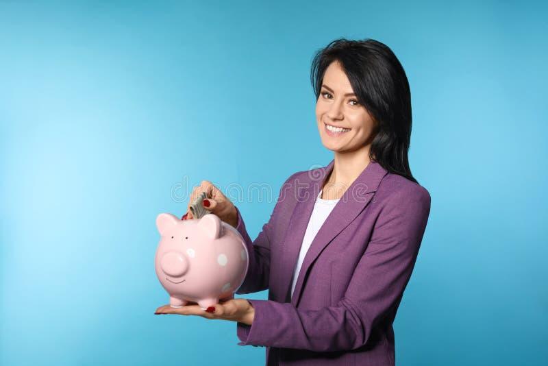 Belle femme d'affaires mettant l'argent dans la tirelire sur le fond de couleur images stock
