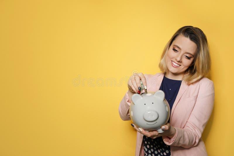 Belle femme d'affaires mettant l'argent dans la tirelire sur le fond de couleur photographie stock libre de droits