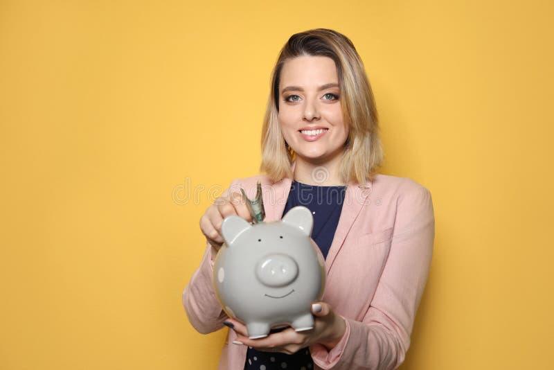 Belle femme d'affaires mettant l'argent dans la tirelire sur le fond de couleur photographie stock