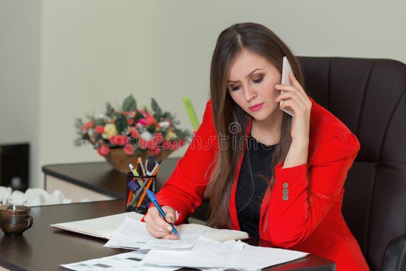 Belle femme d'affaires parlant au téléphone et écrivant sur le papier dans le bureau images stock