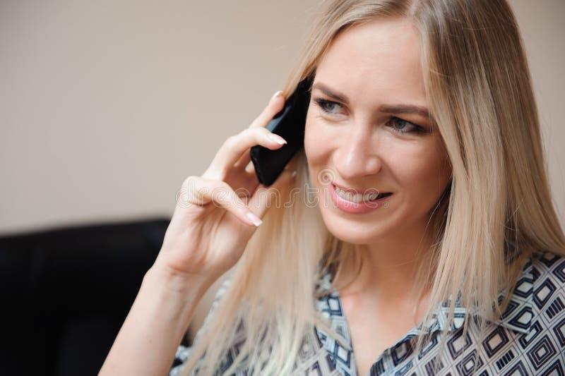 Belle femme d'affaires parlant sur le téléphone portable Jeune travail modèle femelle avec des ventes dans le bureau lumineux photo stock