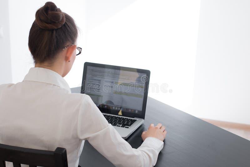 Belle femme d'affaires rêvant tout en travaillant sur l'ordinateur à son bureau image stock