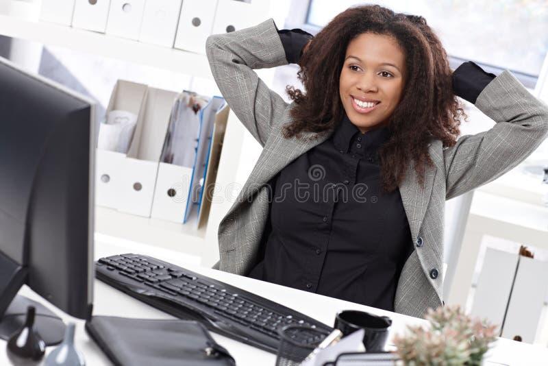 Belle femme d'affaires s'étirant au sourire de bureau image stock