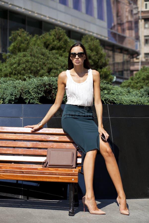 Belle femme d'affaires s'asseyant sur un banc image libre de droits