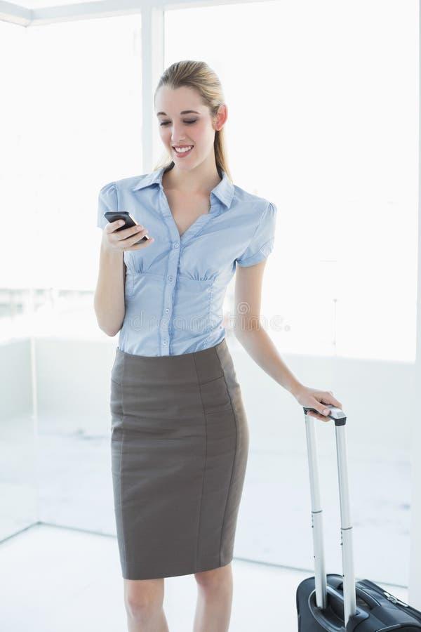 Belle femme d'affaires satisfaite à l'aide de son smartphone se tenant dans son bureau photographie stock libre de droits