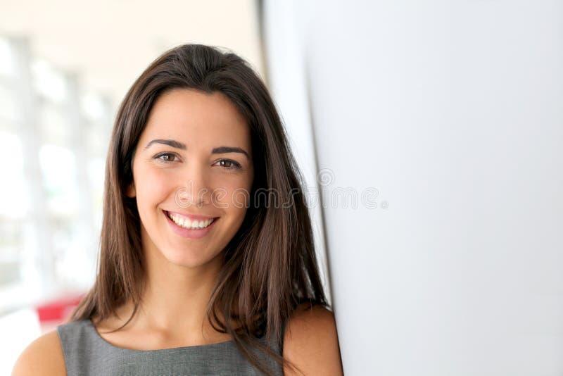 Belle femme d'affaires se penchant sur le mur image stock