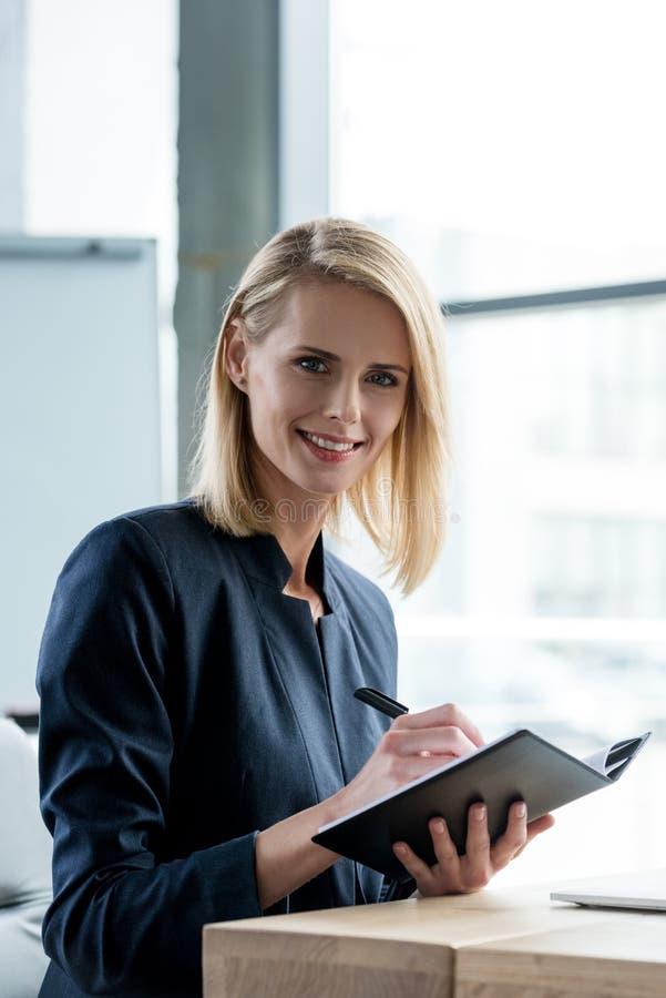 belle femme d'affaires souriant à l'appareil-photo tout en prenant des notes image stock