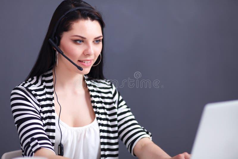 Belle femme d'affaires travaillant à son bureau avec le casque et l'ordinateur portable photos stock