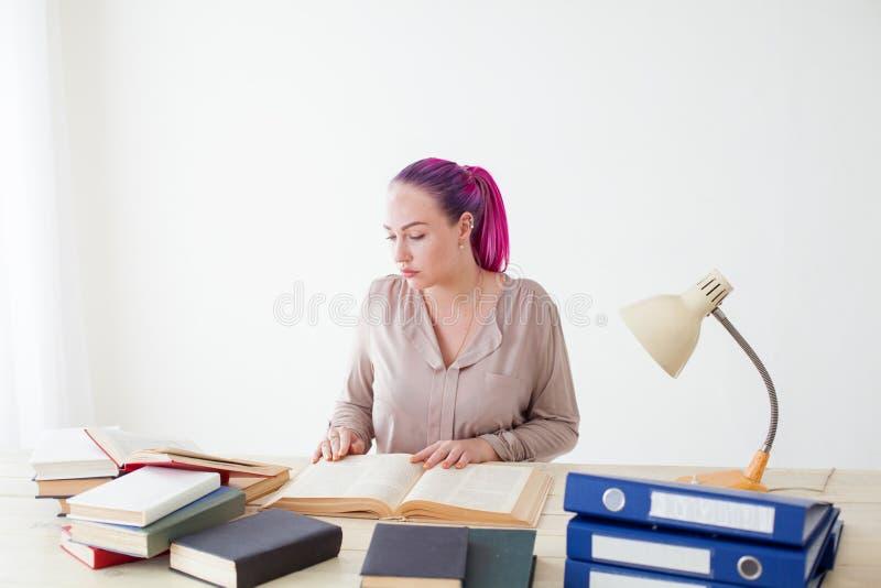 Belle femme d'affaires travaillant dans un bureau derrière une table avec des livres images libres de droits