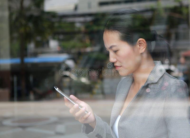 Belle femme d'affaires utilisant un smartphone au verre de réflexion d'immeuble de bureaux images libres de droits