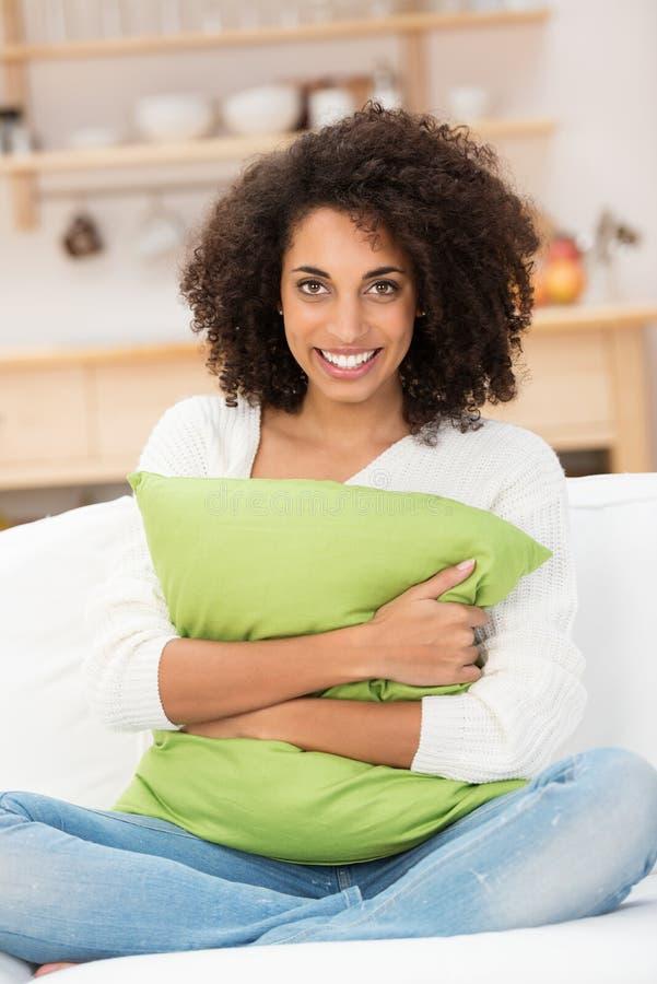 Belle femme d'Afro-américain étreignant un oreiller photographie stock