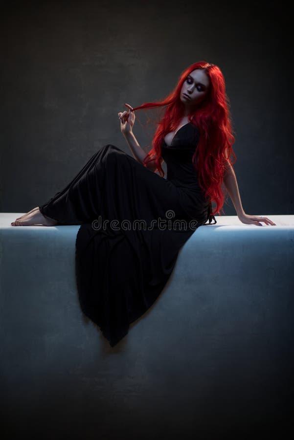 Belle femme d'une chevelure rouge dans la robe noire photographie stock libre de droits