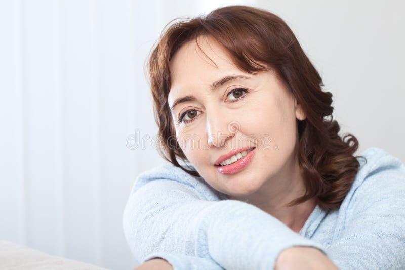 Belle femme d'une cinquantaine d'années de brune avec un sourire de lancement se reposant sur un sofa à la maison regardant la ca photos stock