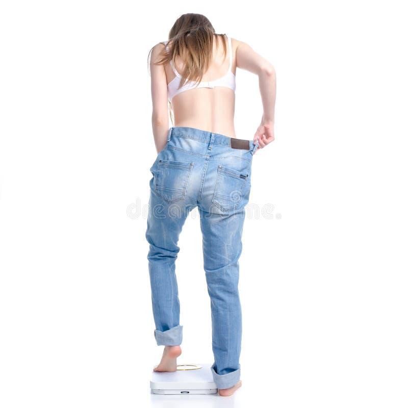 Belle femme dans de grands jeans sur la peser-machine, r?gime de perte de poids photos stock