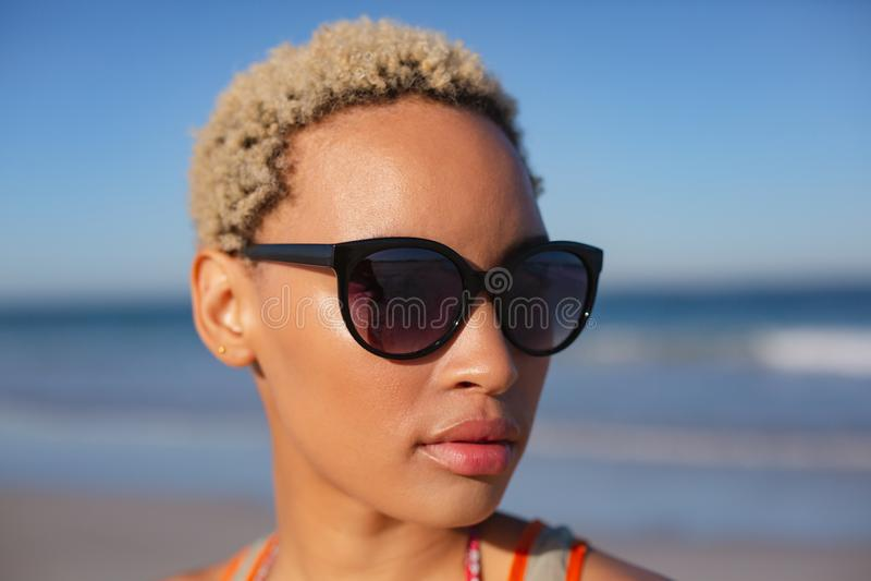 Belle femme dans des lunettes de soleil regardant loin sur la plage au soleil photographie stock