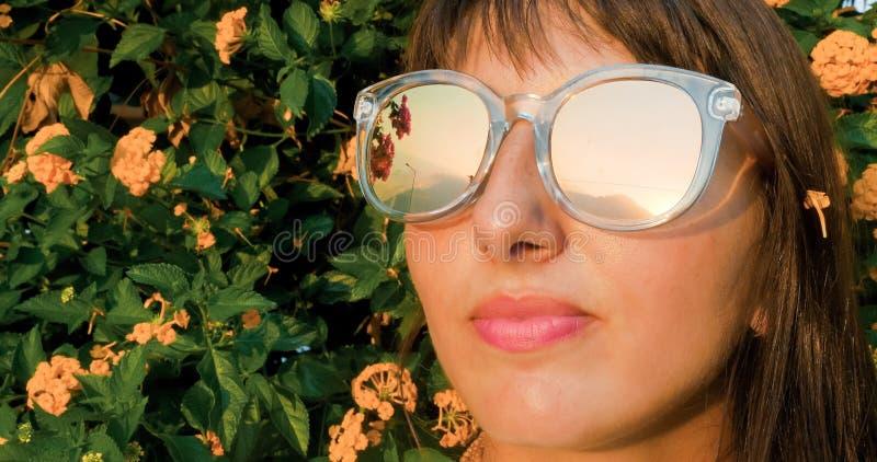Belle femme dans des lunettes de soleil se tournant vers le soleil images stock