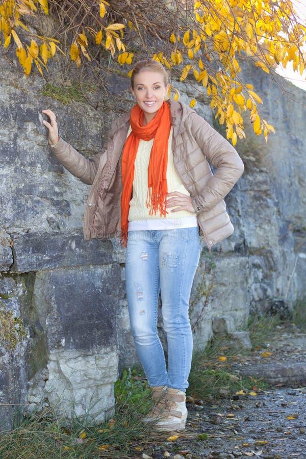 Belle femme dans des vêtements chauds posant contre le mur en pierre photographie stock libre de droits