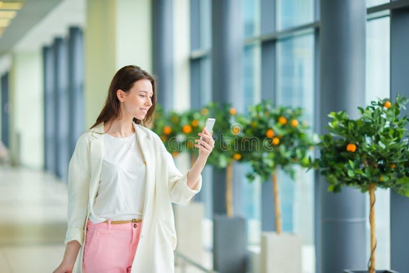 Belle femme dans l'aéroport international Touriste avec le smartphone d'intérieur photo stock