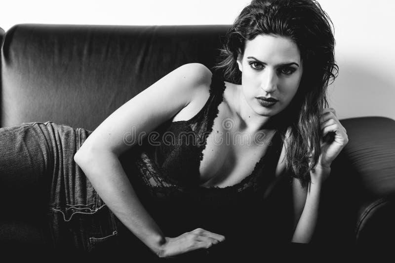 Belle femme dans la lingerie noire s'étendant sur un divan image libre de droits