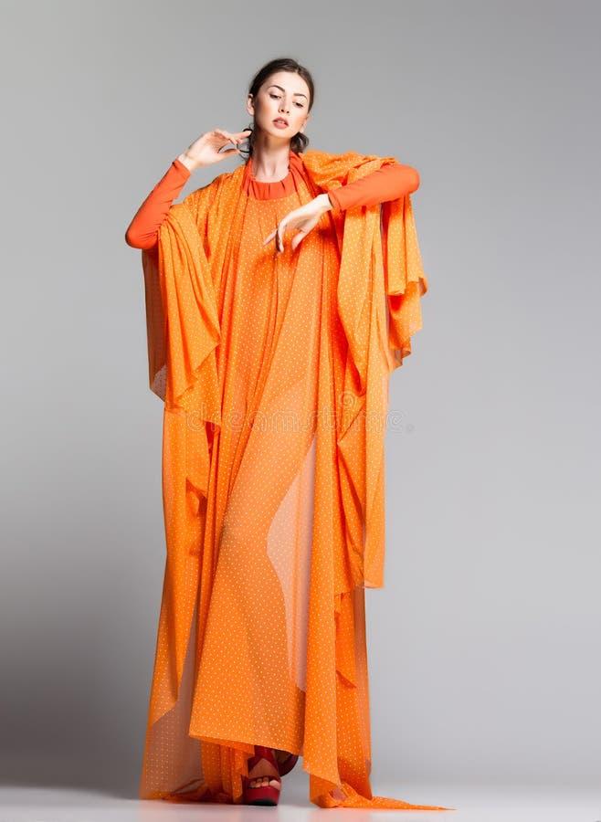 Belle femme dans la longue pose orange de robe excessive dans le studio image stock