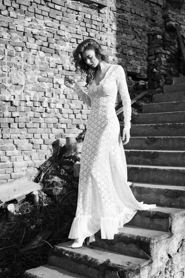 Belle femme dans la pose blanche de robe extérieure photographie stock