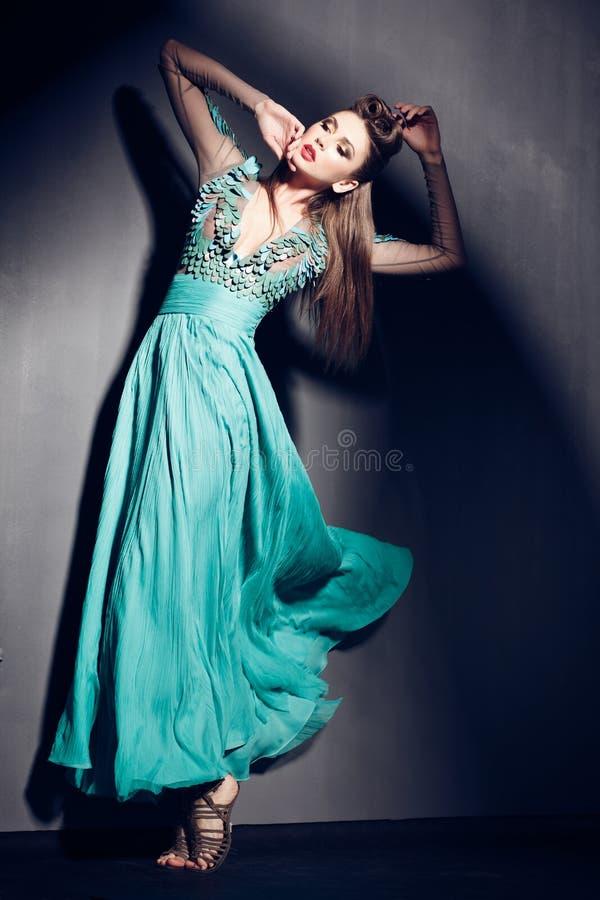 Belle femme dans la pose verte de robe excessive à l'intérieur image libre de droits