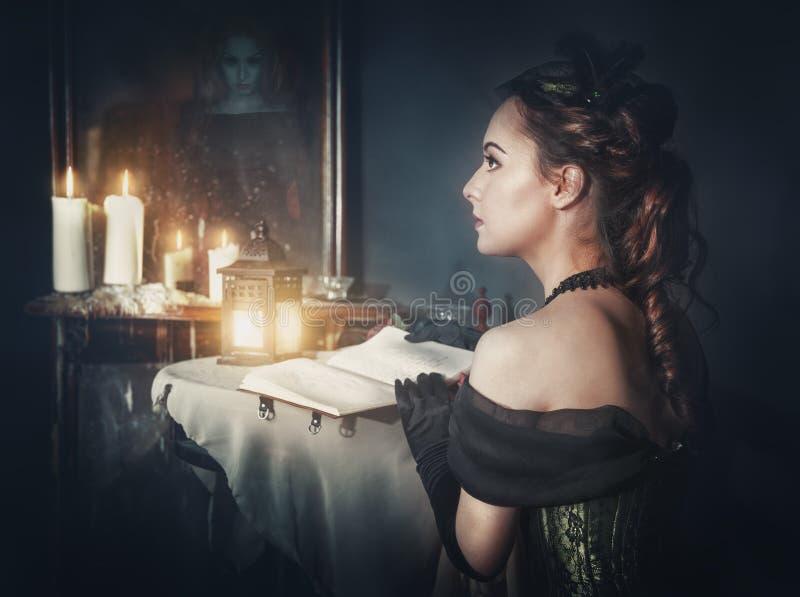 Belle femme dans la rétro robe et le fantôme dans le miroir images stock