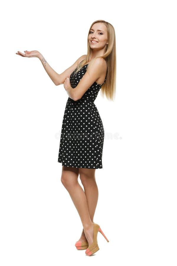 Belle femme dans la robe affichant l'espace vide de copie photo stock