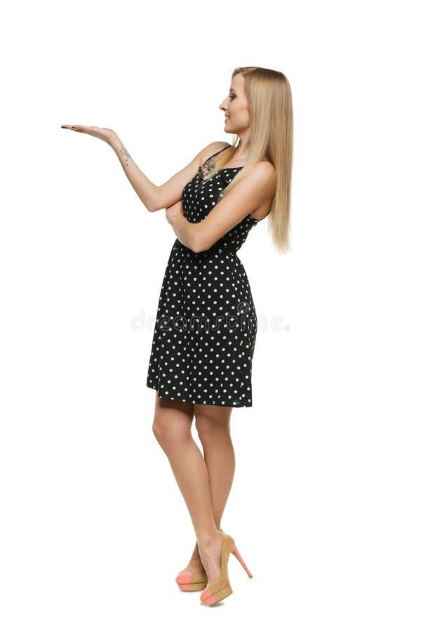 Belle femme dans la robe affichant l'espace vide de copie sur sa paume image libre de droits