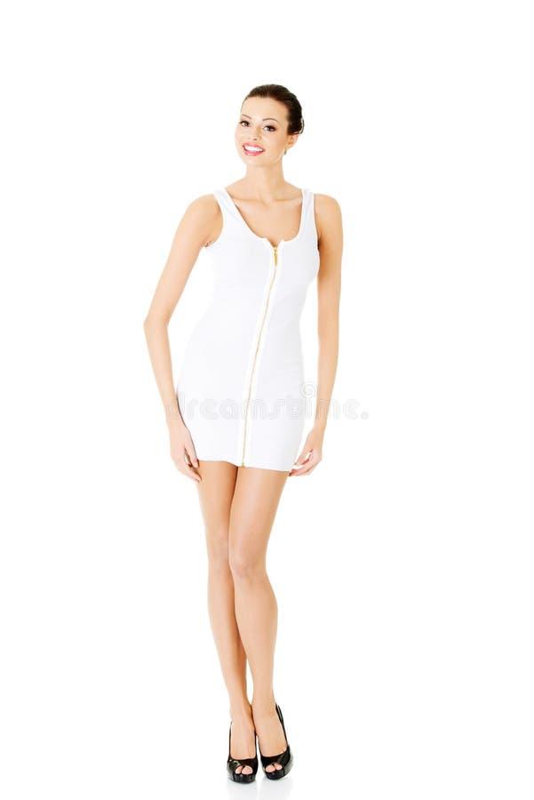 Belle femme dans la robe blanche et des talons hauts noirs. photographie stock libre de droits