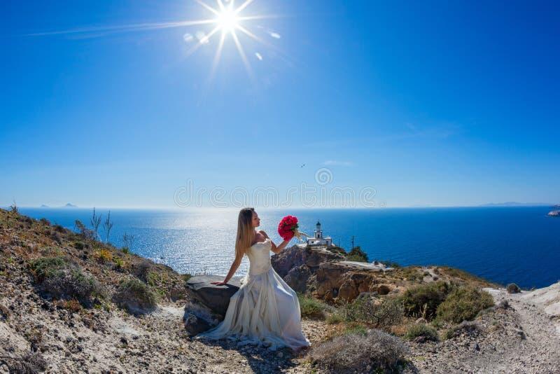 Belle femme dans la robe blanche sur une pierre photo stock