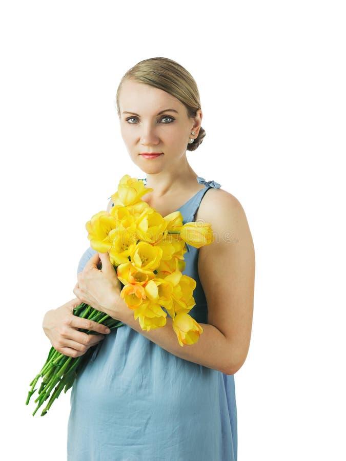 Belle femme dans la robe bleue avec le bouquet des tulipes photographie stock libre de droits