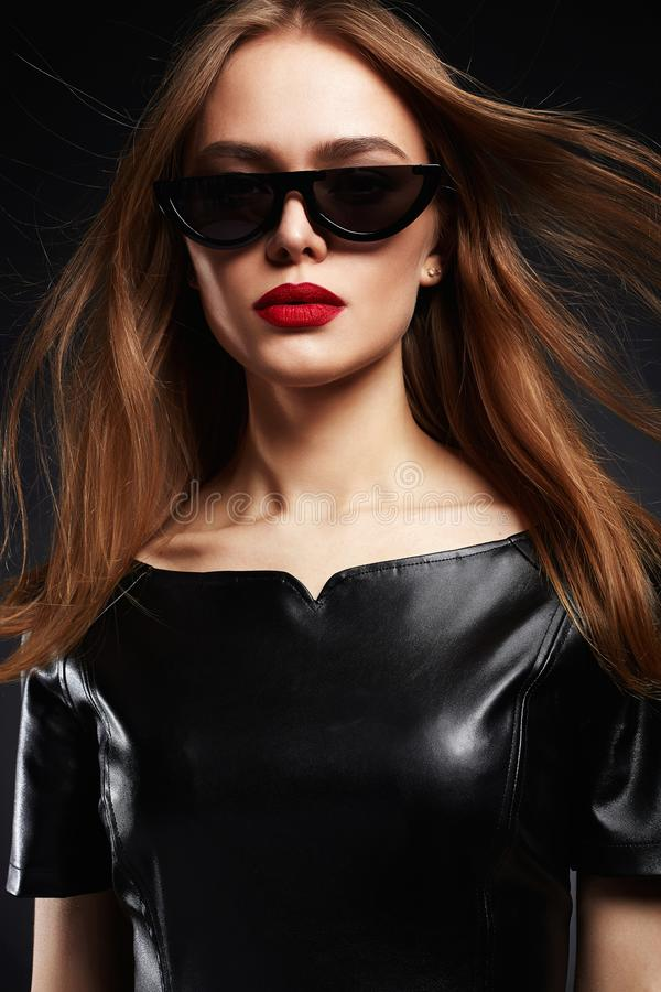 Belle femme dans la robe de lunettes de soleil et de cuir photos libres de droits