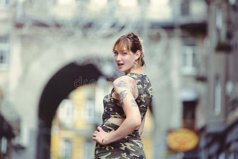 Belle femme dans la robe de militaires dans la ville et tatouage sur des mains image libre de droits