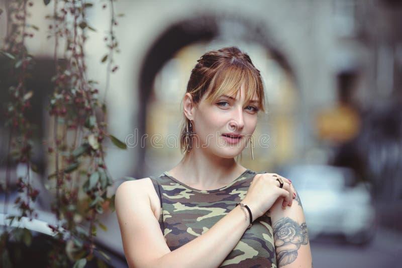 Belle femme dans la robe de militaires dans la ville et tatouage sur des mains images stock