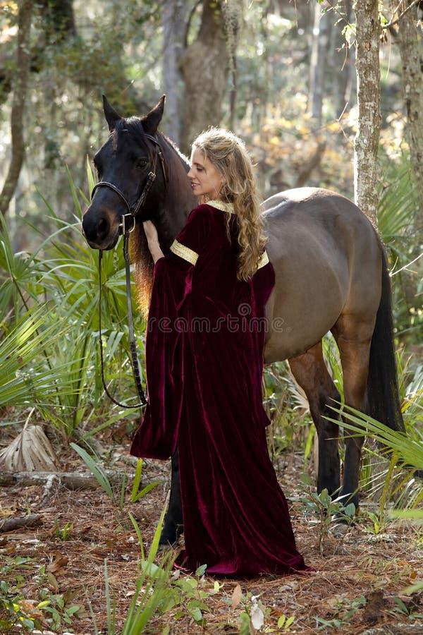 Belle femme dans la robe formelle et le cheval photos stock