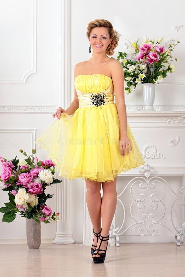 Belle femme dans la robe jaune dans le studio de luxe. images libres de droits