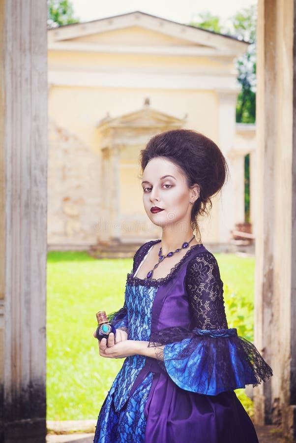 Belle femme dans la robe médiévale avec la bouteille de parfum photo stock