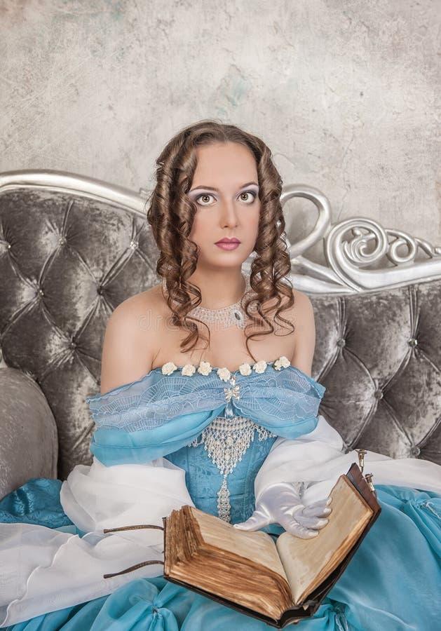 Belle femme dans la robe médiévale avec le livre sur le sofa images libres de droits