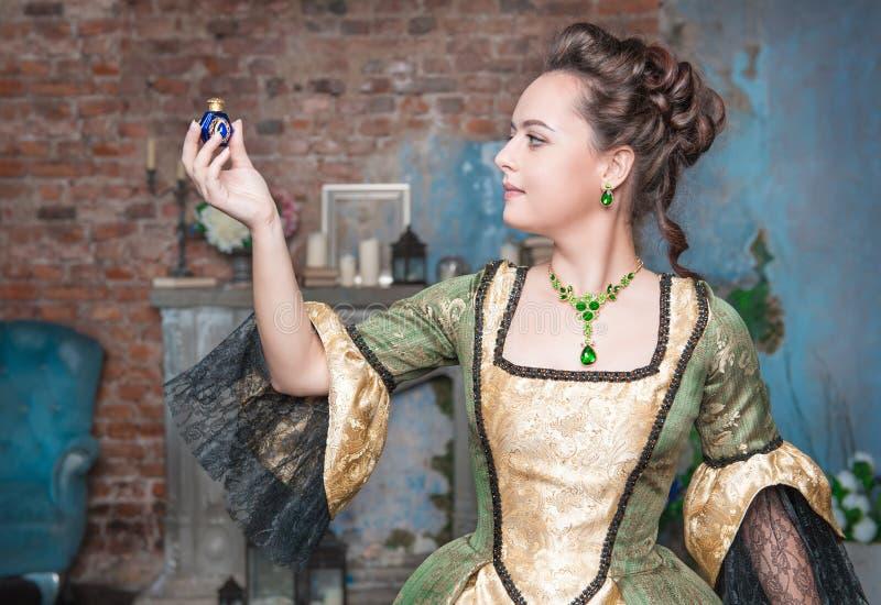 Belle femme dans la robe médiévale avec peu de bouteille photo stock