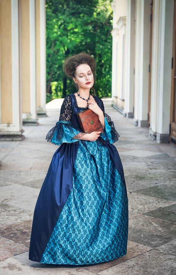 Belle femme dans la robe médiévale bleue avec le livre photos stock