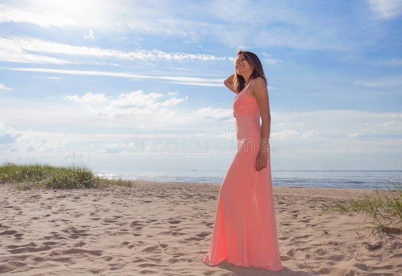Belle femme dans la robe rose sur la plage sablonneuse photographie stock