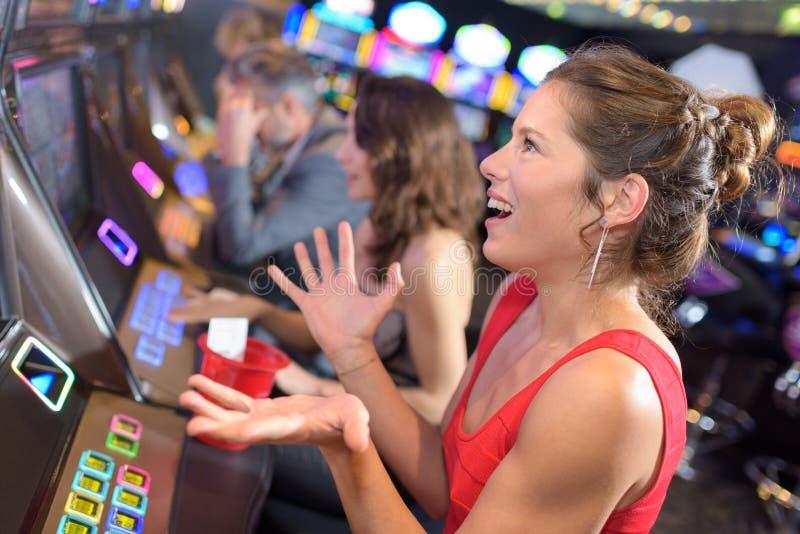Belle femme dans la robe rouge jouant la machine à sous images libres de droits