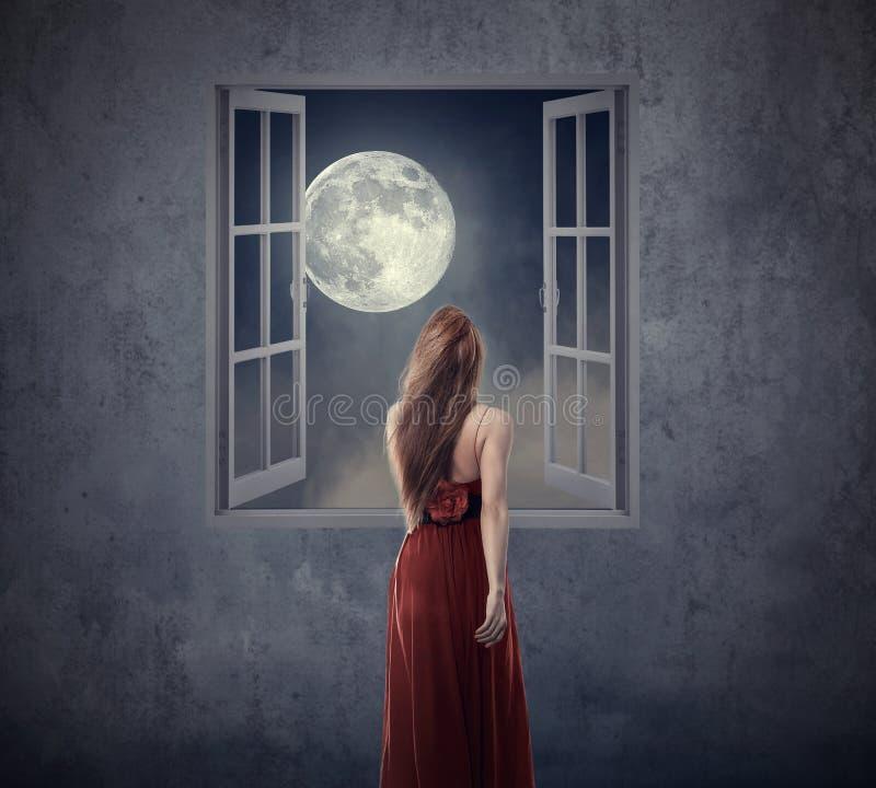 Belle femme dans la robe rouge marchant à la fenêtre ouverte avec la lune photographie stock