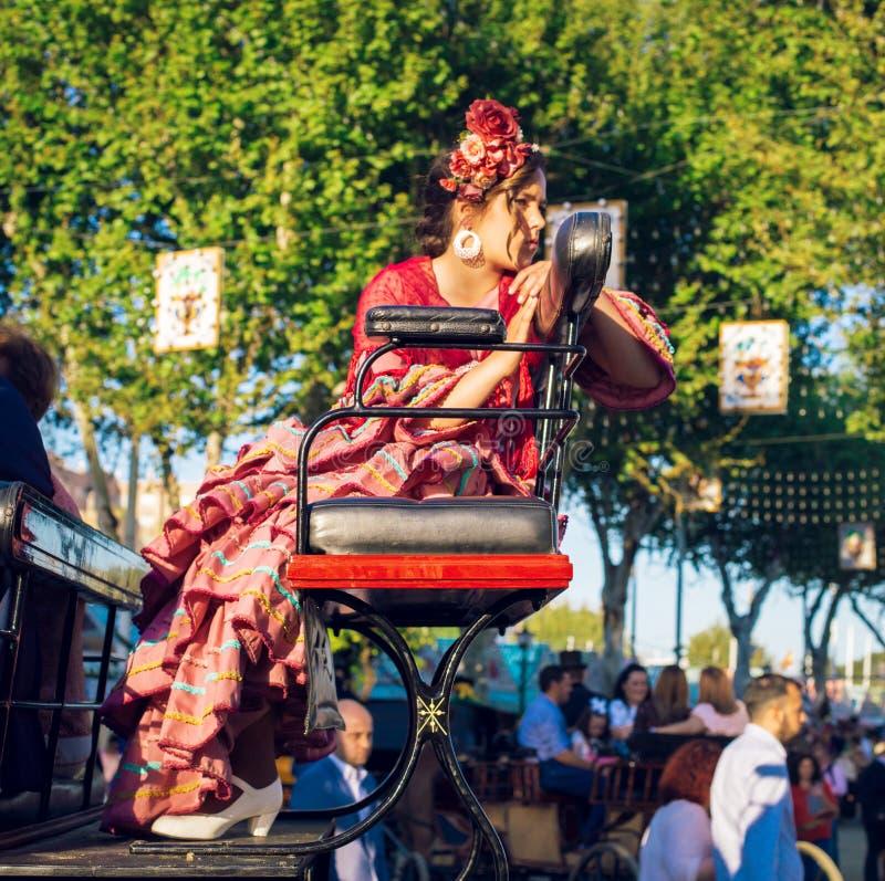 Belle femme dans la robe traditionnelle et colorée voyageant dans chariots hippomobiles chez April Fair, foire de Séville photo libre de droits